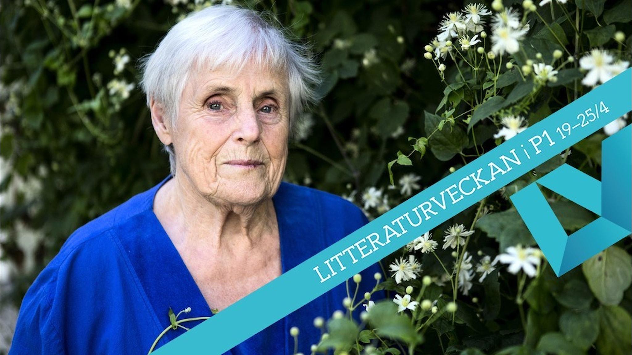 Porträtt av författaren Elsie Johansson, klädd i en blå tröja stående intill en grönskande buske med vita blommor.