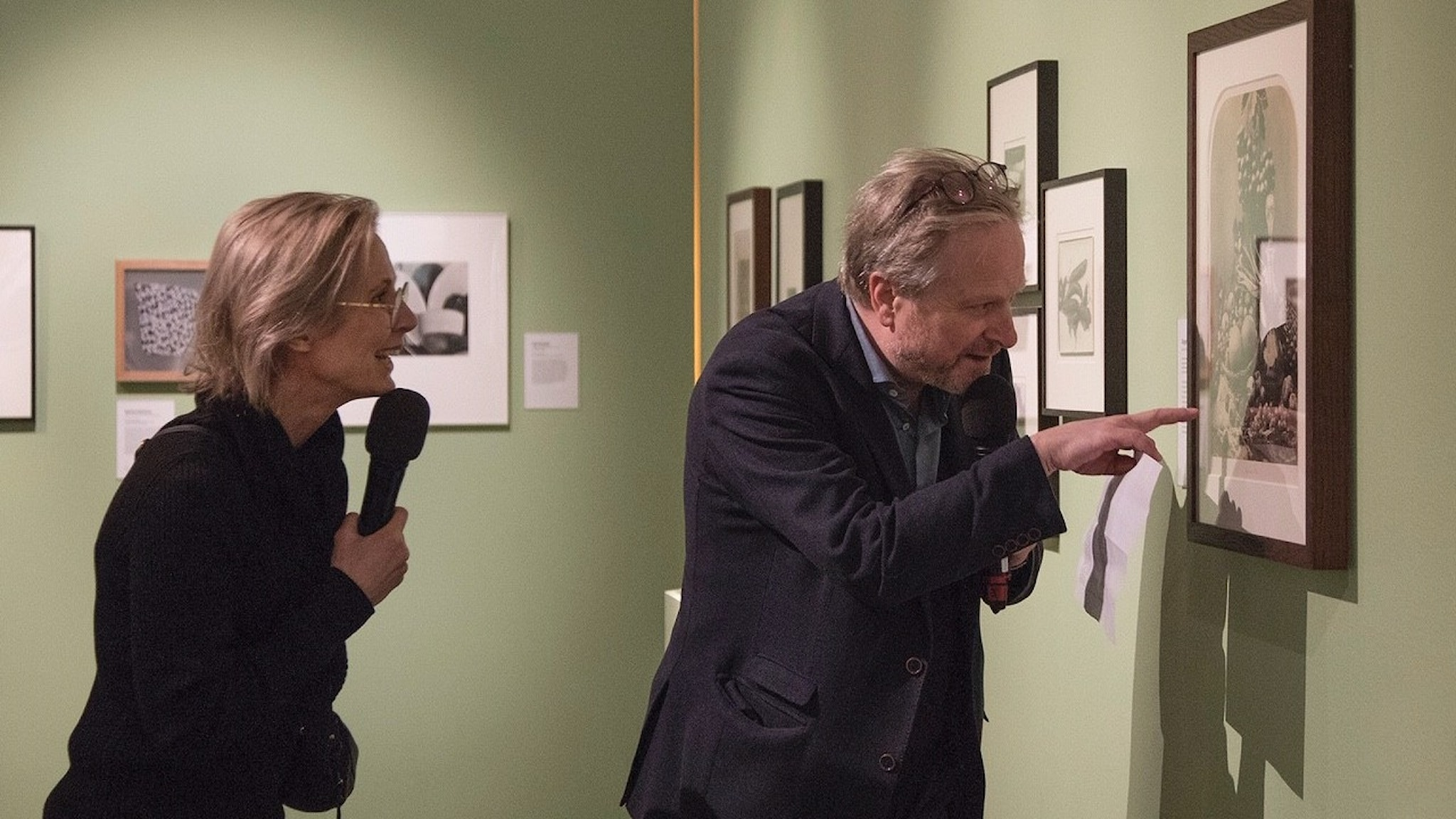 Fotohistorikern Julia Tedroff och programledaren Karsten Thurfjell studerar ett matfotografi.