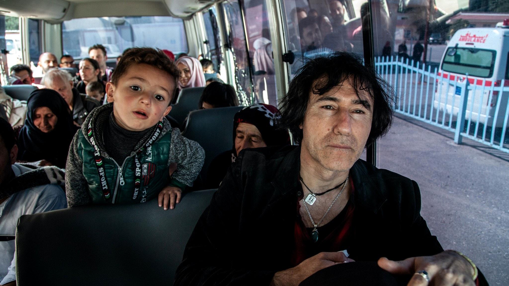 En man som vill rädda sina barnbarn ur ett flyktingläger sitter på en buss i Irak. En liten pojke bakom honom tittar fram över sätet.