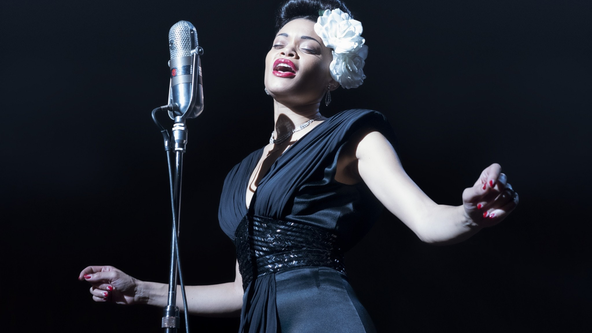 Andra Day i rollen som Billie Holiday, sjunger bakom en stor mikrofon och har en stor gardenia bakom örat