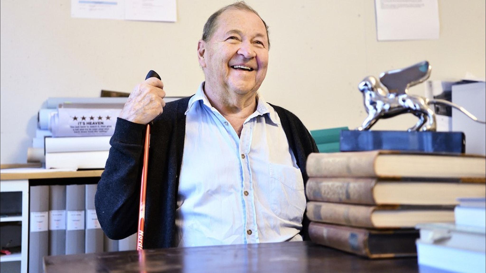 Filmregissören Roy Andersson klädd i ljus skjorta och mörk kofta sitter vid ett skrivbord och ler.