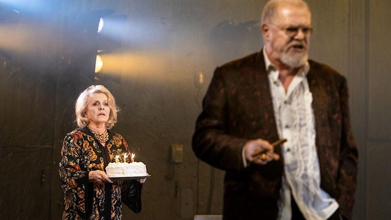 Marie Göranzon bär en tårta och Peter Andersson ser arg ut i Katt på hett plåttak.