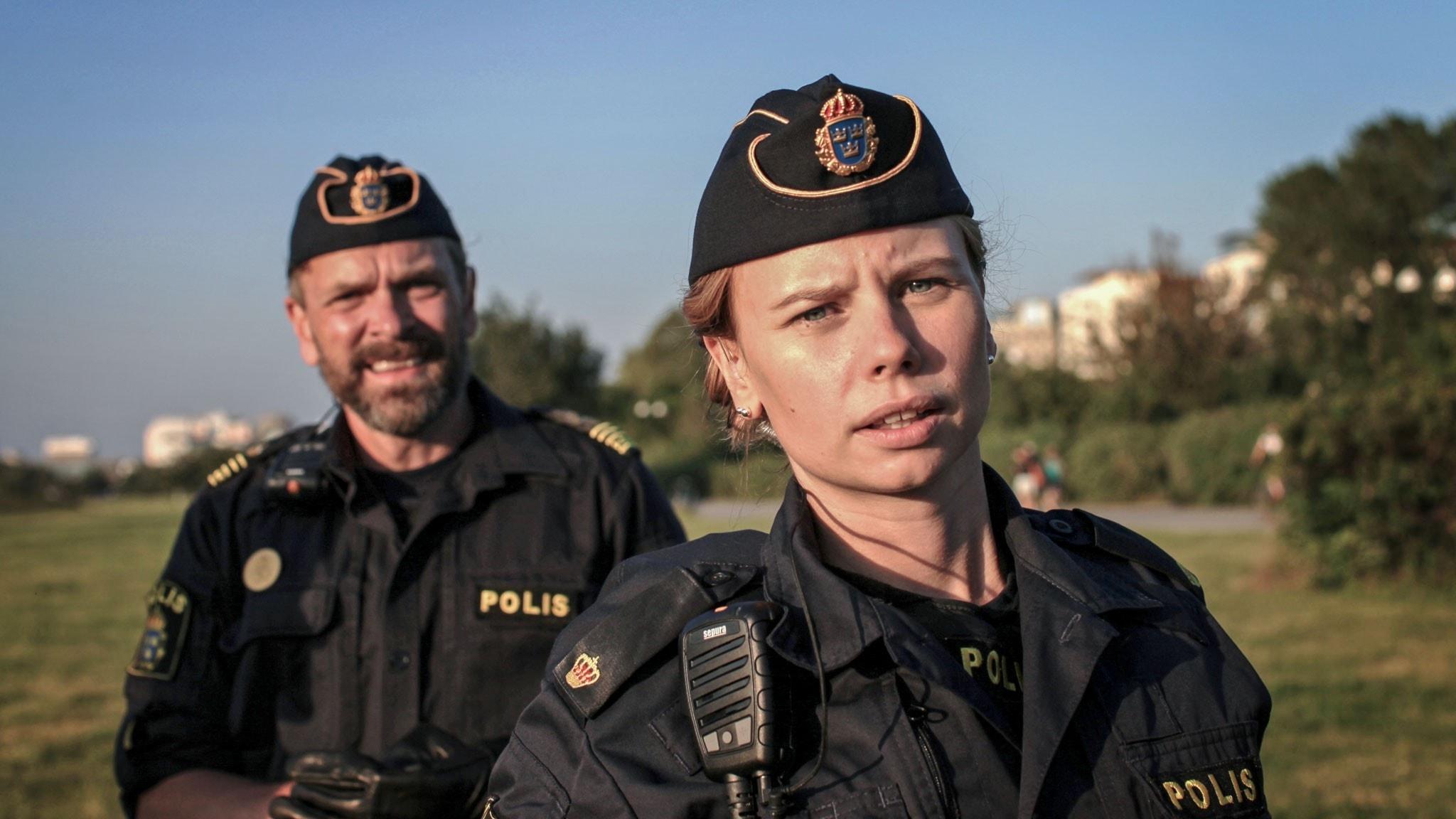 En kvinnlig och en manlig polis står utomhus och blickar in i kameran.