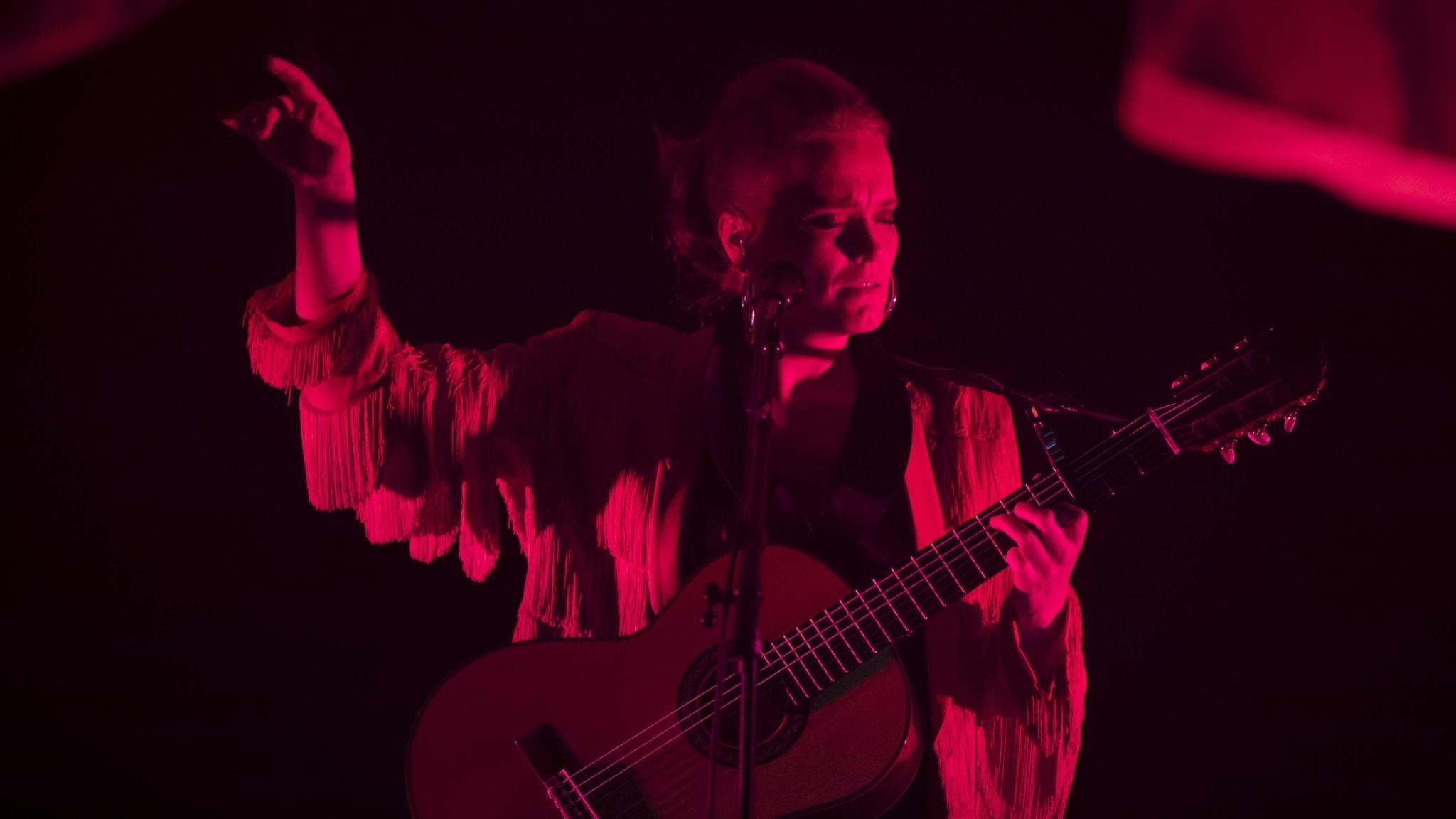 Ane Brun står på scenen med sin gitarr runt halsen på väg att ta ett ackord i ett rött ljus