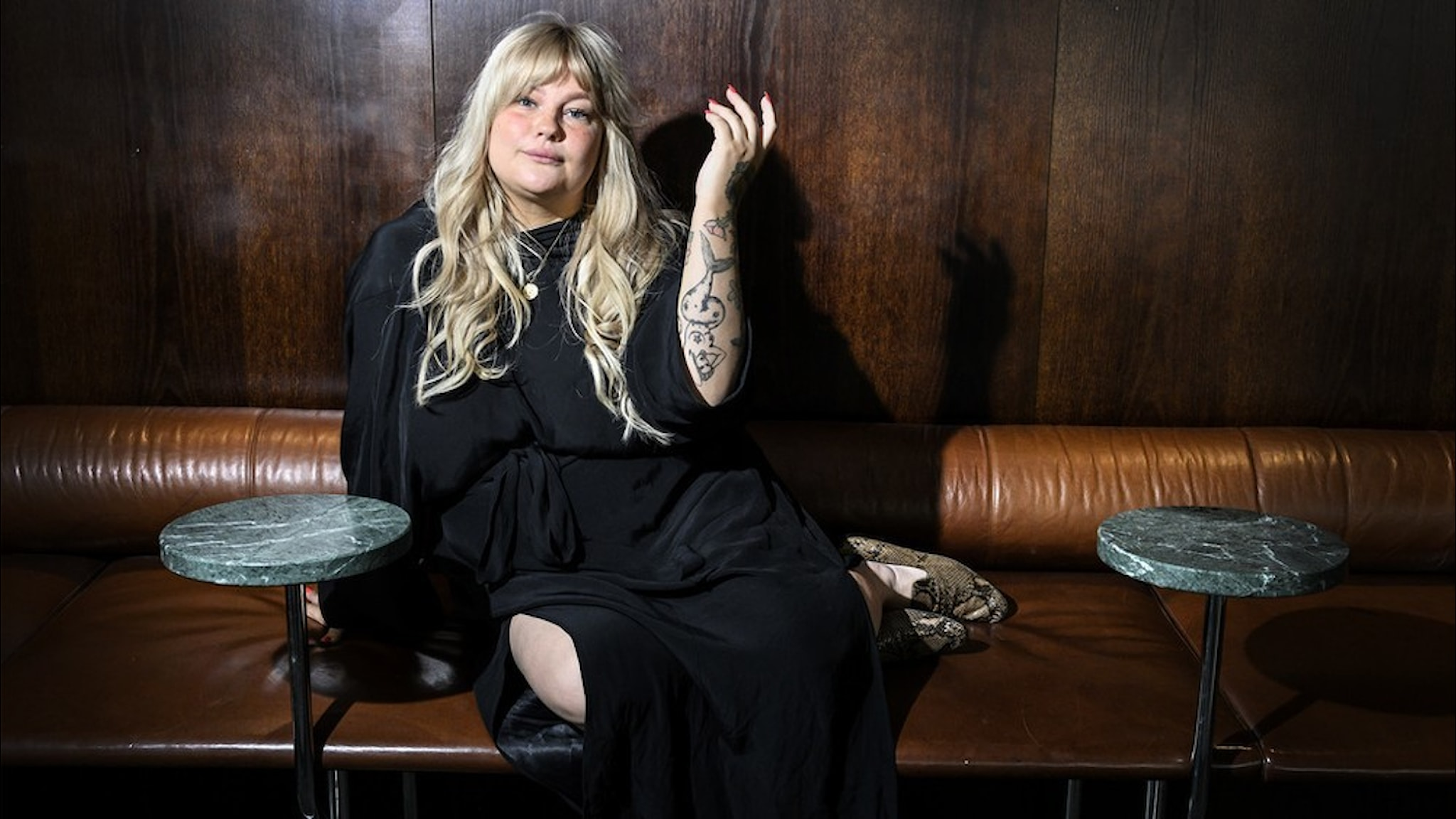 Artisten Sarah Klang sitter vid ett kafébord, klädd i svart.