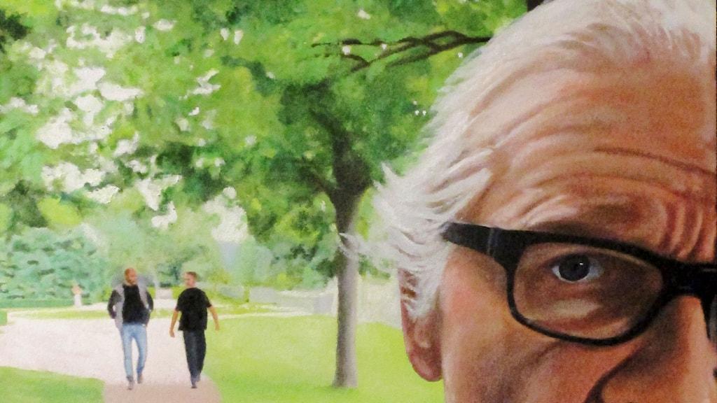 En självpoträtt av konstnären Lars Vilks0 i parkmiljö där man se hans livvakter i bakgrunden.