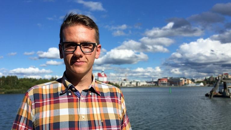En man med en rutig skjorta och glasögon står mot en silhuett av Göteborg