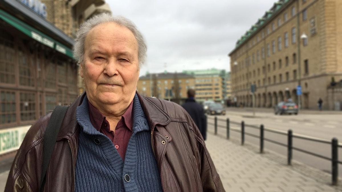 En äldre man med skinnjacka står på gatan