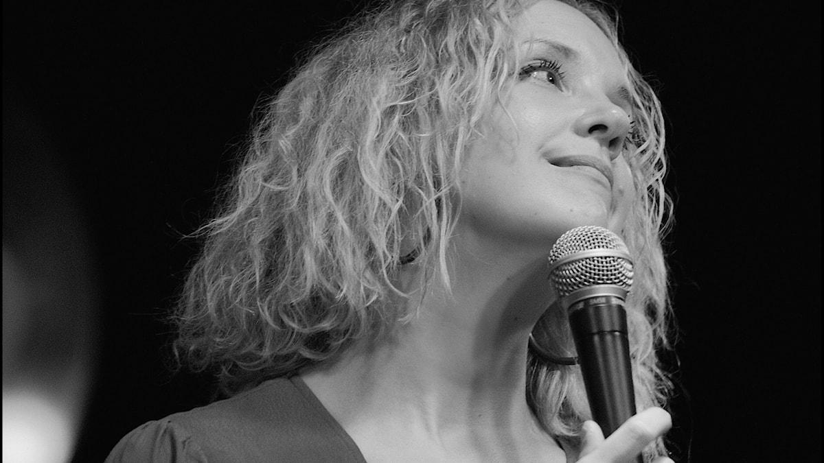 Vaaleatukkainen Sanna Ruohoniemi mustavalkokuvassa mikrofonin kanssa katsoo yläviistoon. Kuva: Pressfoto