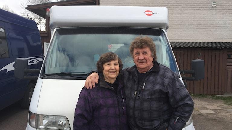 Eila ja Paavo Niva seisovat asuntoautonsa edessä tummat takit päällään.