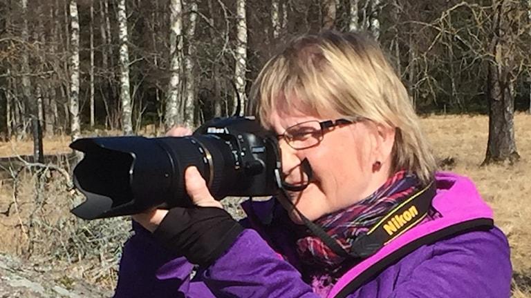 Tarja Huttusella on violetti takki ja pitkäputkinen kamera, jolla kuvaa.