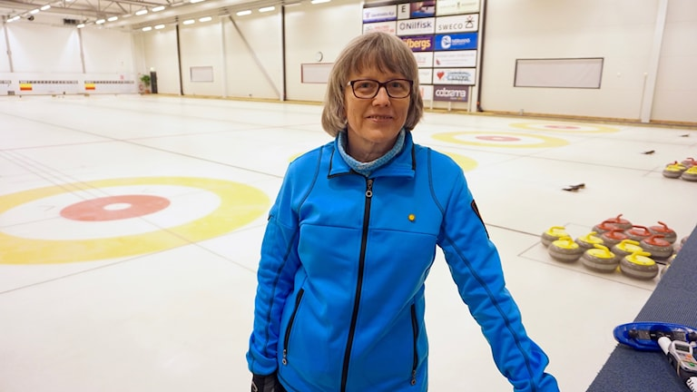 Kuvassa silmälasipäinen nainen nojaa curling-rinkkiä vastaan.