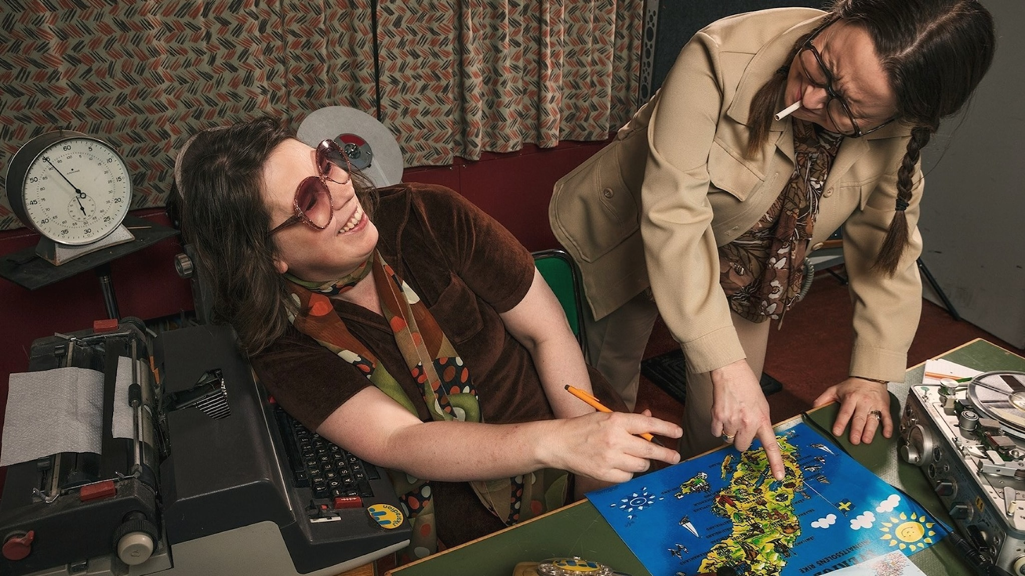 Christel och Lena pekar på en karta och skrattar.