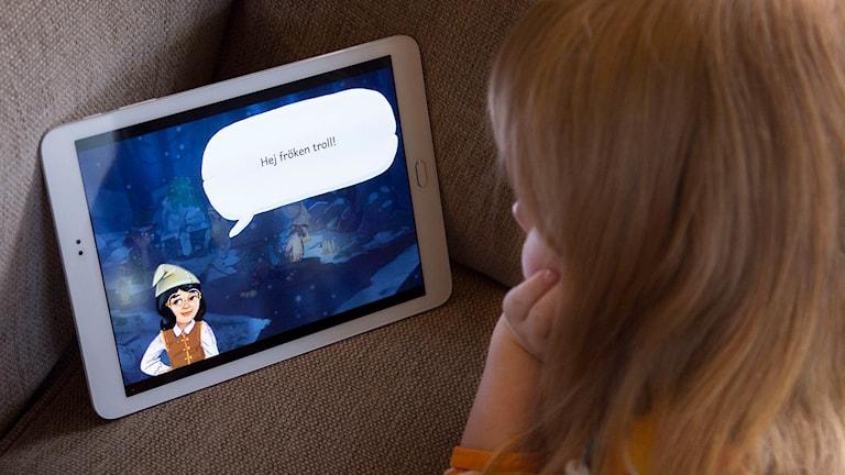 """Ett barn kollar på en surfplatta med Marvinter-spelet. Hustomten Jenny från spelet säger """"Hej fröken troll!"""""""