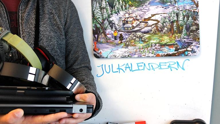Någon håller i flera hörlurar, en dator och surfplattor framför en whiteboard som årets julkalender är uppsatt på.
