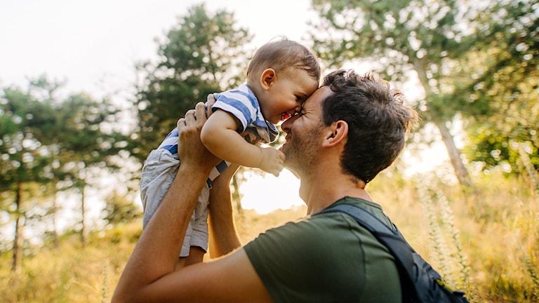 En pappa som lyfter sitt barn. Båda ler.