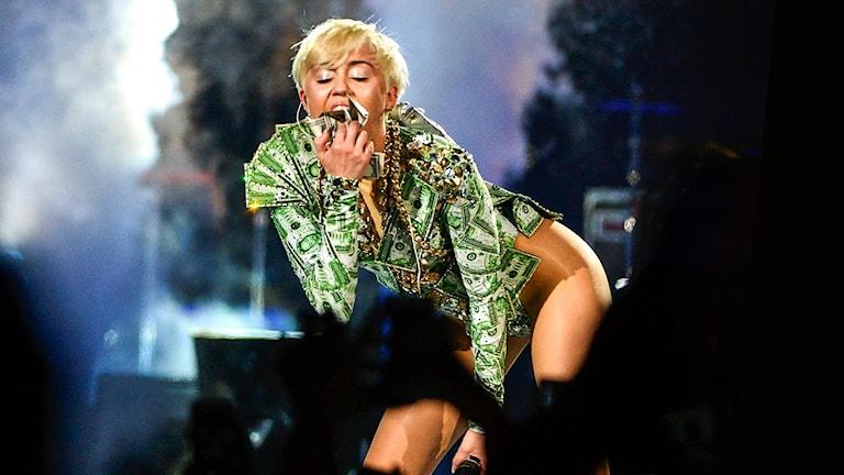 Miley Cyrus iklädd en topp som ser ut som att den är gjord av pengar.