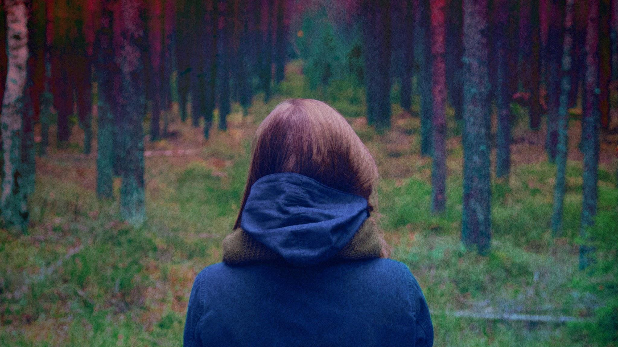 Flicka med rött hår står i skog med ryggen mot kameran.