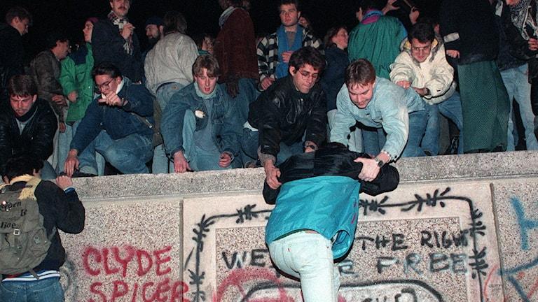 Tusentals människor klättrade  upp på muren vid Brandenburger Tor i Västberlin på fredagskvällen 10 november 1989.