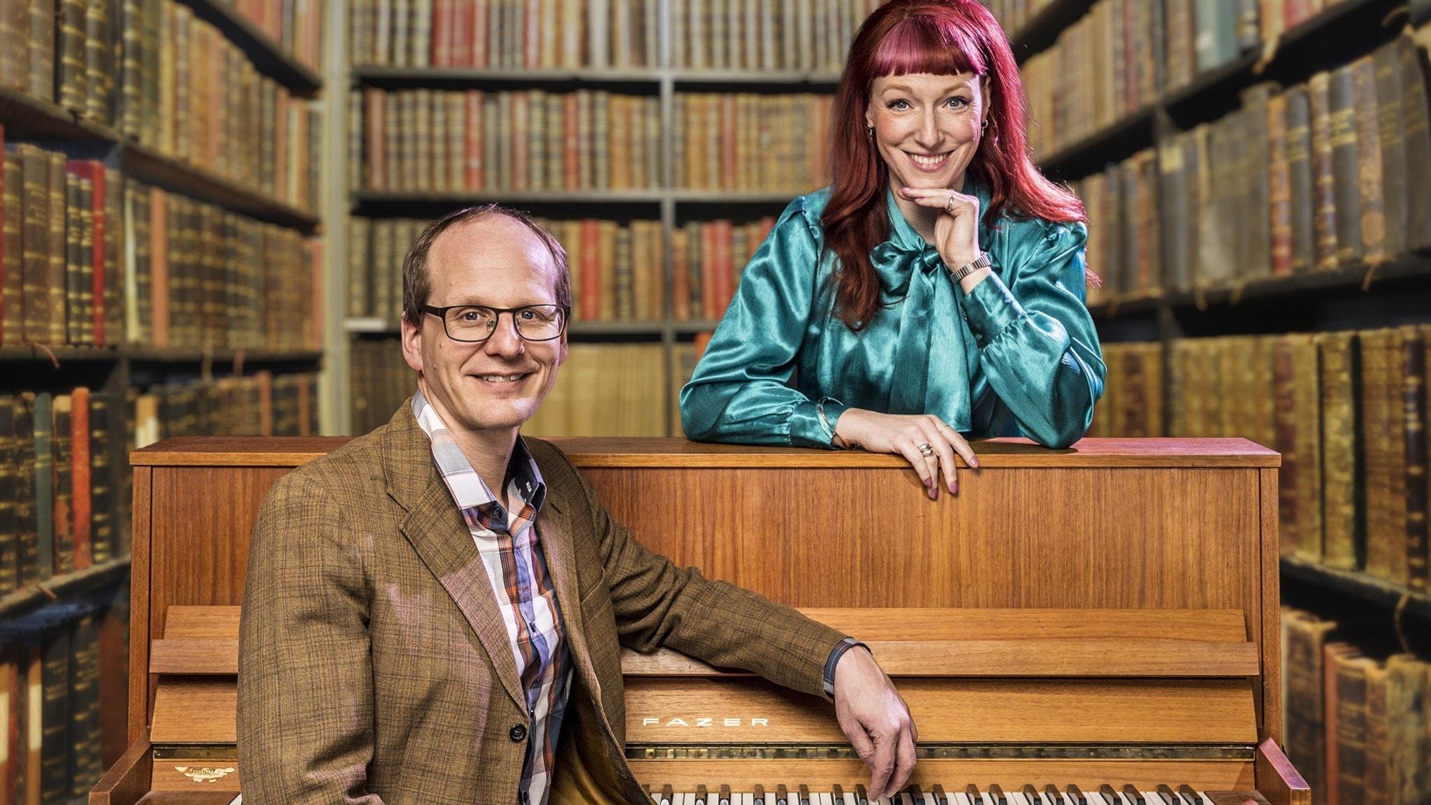 Programledarna Mattias Lundberg och Josefin Johansson står fram ett piano med böcker i bakgrunden.