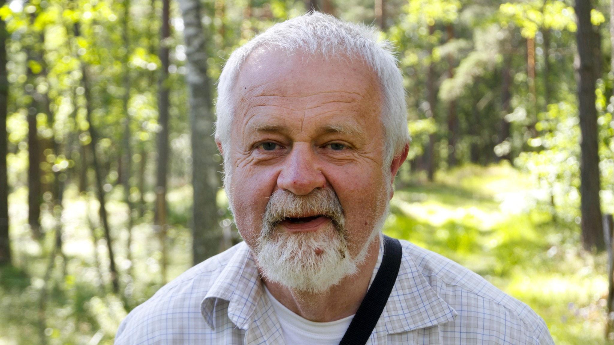 Porträttbild av en glad herre med vitt hår och vitt hakskägg