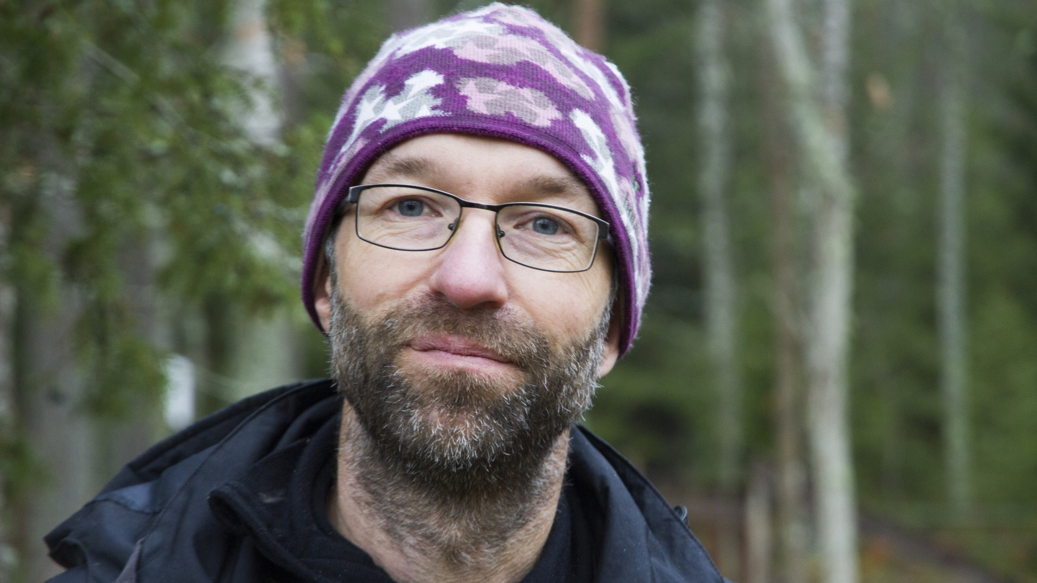 En porträttbild av en skäggig man i glasögon och stickad mössa