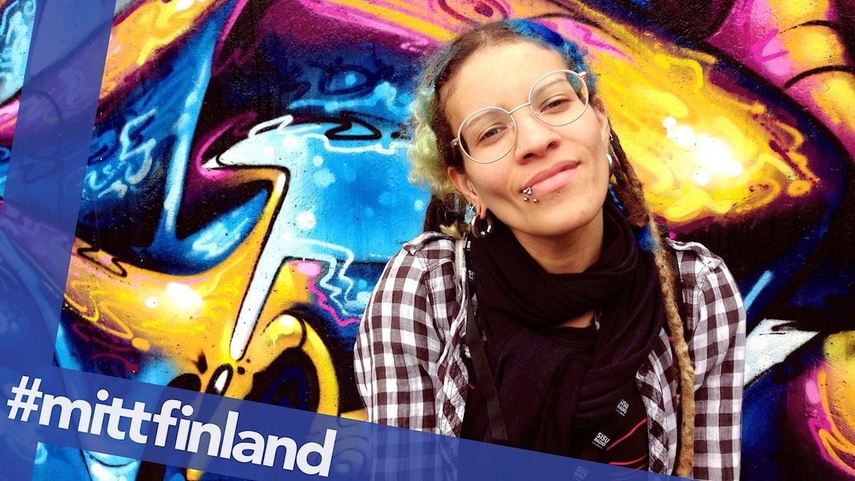En kvinna med glasögon och en färgglad vägg bakom