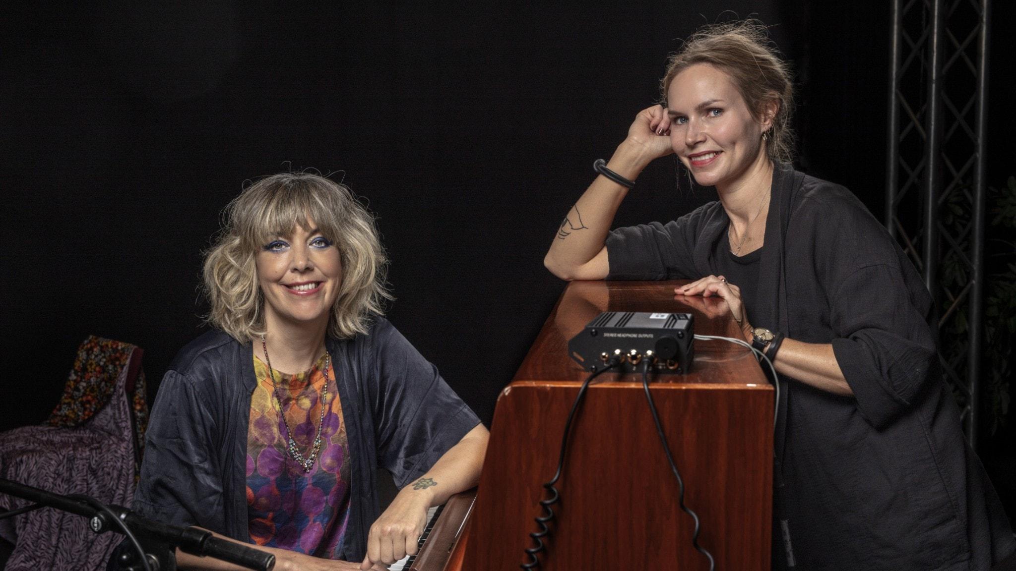 Nina Persson står till höger och lutar sig mot ett brunt piano. Marit Bergman sitter vid pianot.