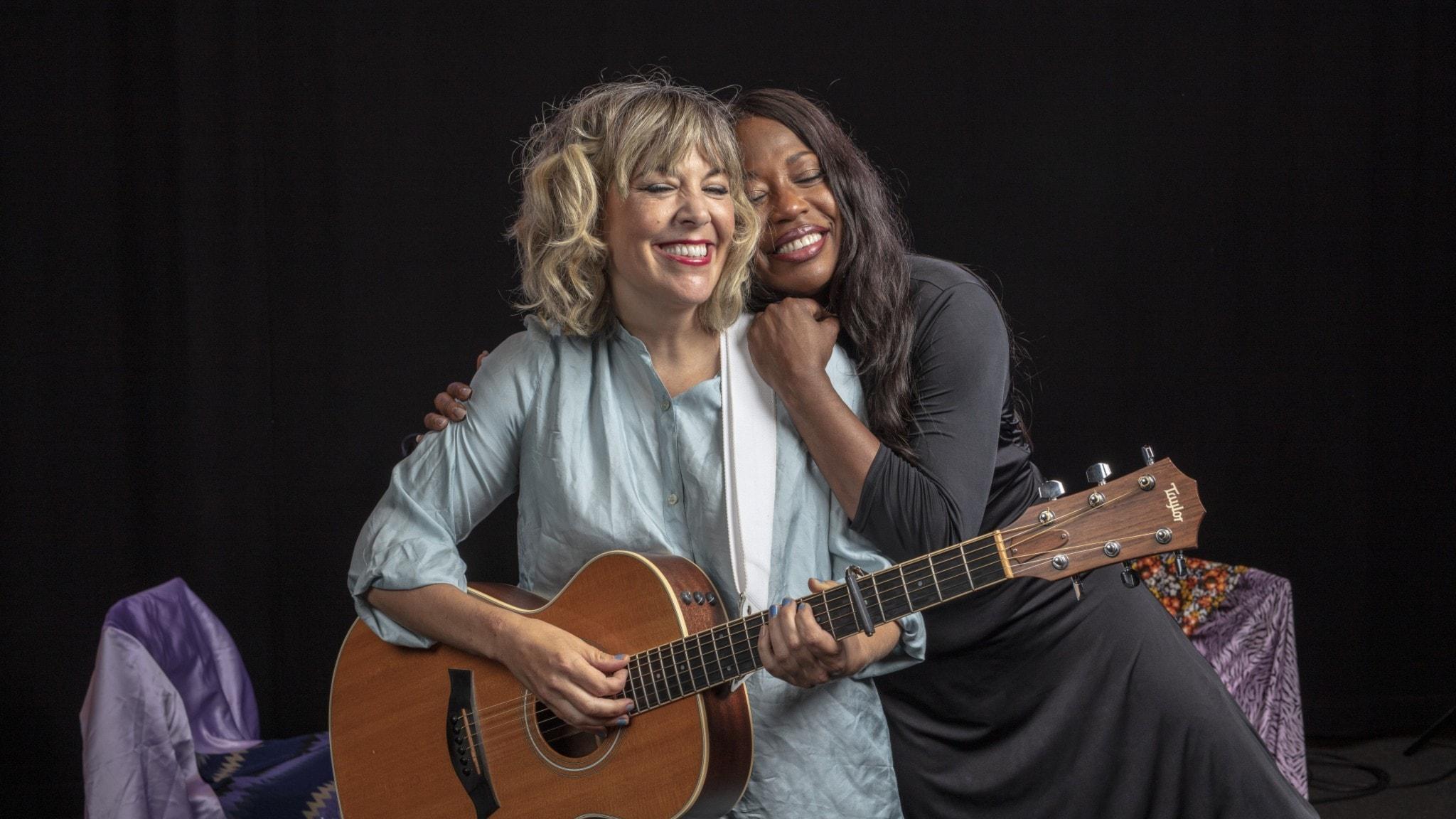Marit Bergman och LaGaylia Frazier kramar om varandra. Marit har gitarr i famnen.