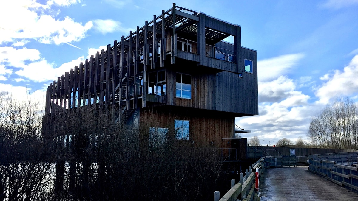 Ett brunt trevåningshus i mörkt trä. Huset är fyrkantigt men övervåningarna sticker ut lite från undervåningen.