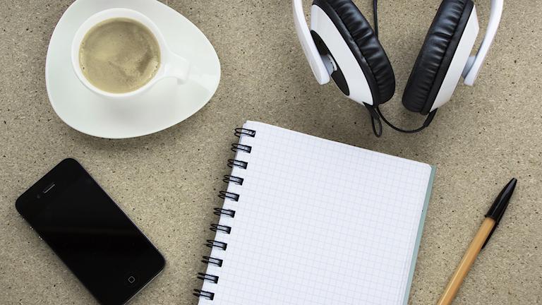En kaffekopp, hörlurar, mobiltelefon, anteckningsblock och penna.