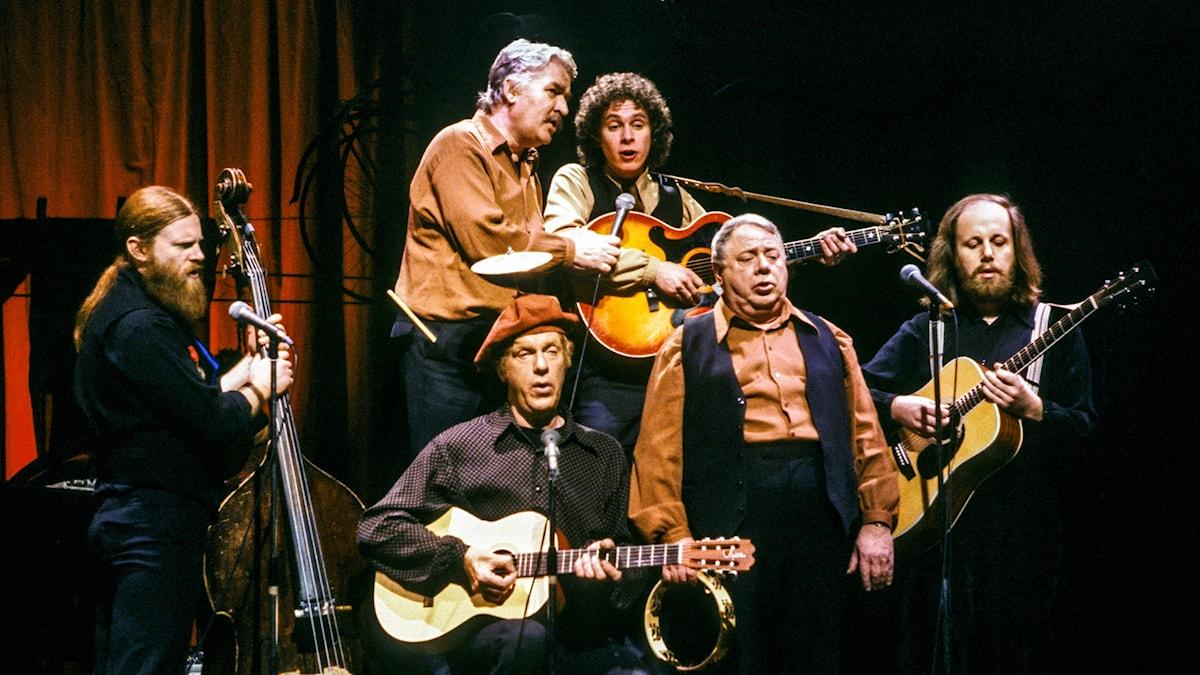Manusförfattarna och komikerna Hans Alfredson (2:a fr. v.) och Tage Danielsson (3:a fr. v.) spelar med orkestern och dess kapellmästare Gunnar Svensson (5:a fr. v.) i deras lunchrevy Under dubbelgöken på Berns i Stockholm 1979.