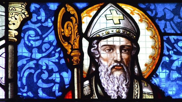 Målat glasfönster med en biskop i mitra som motiv.