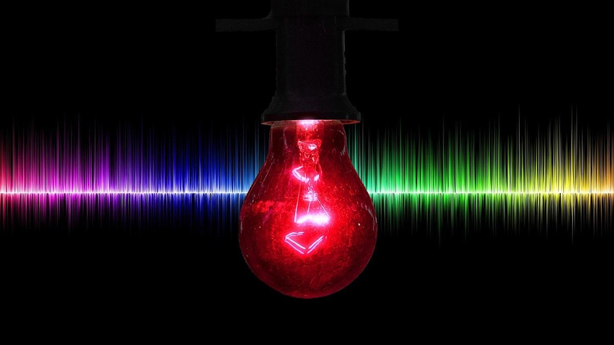 Röd lampa lyser i förgrunden. I bakgrunden regnbågsfärgade ljudvågor.