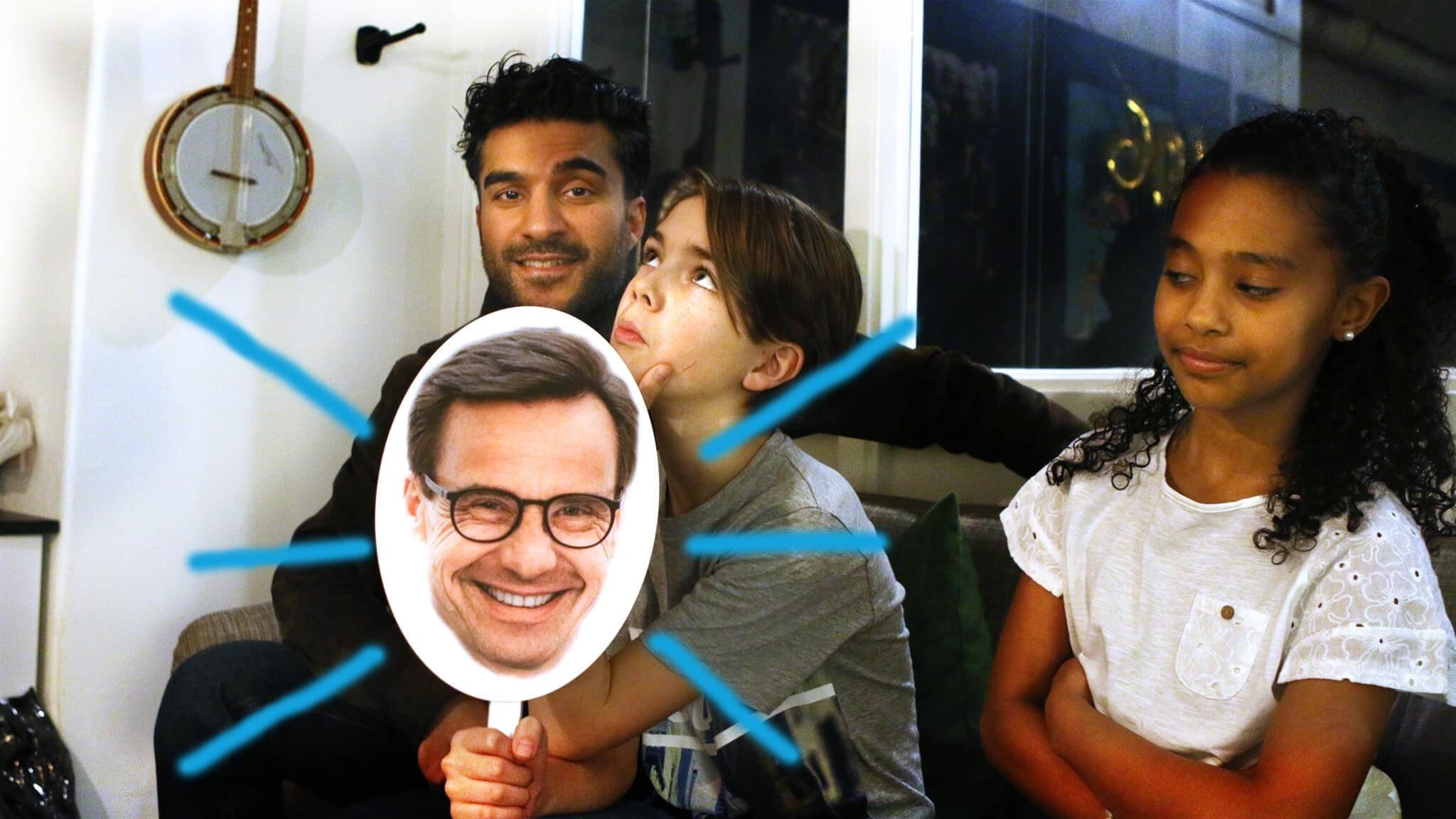 Nils, Negwa och Farzad sitter i en soffa. Nils håller i en pappfigur av Moderaternas partiledare Ulf Kristersson.