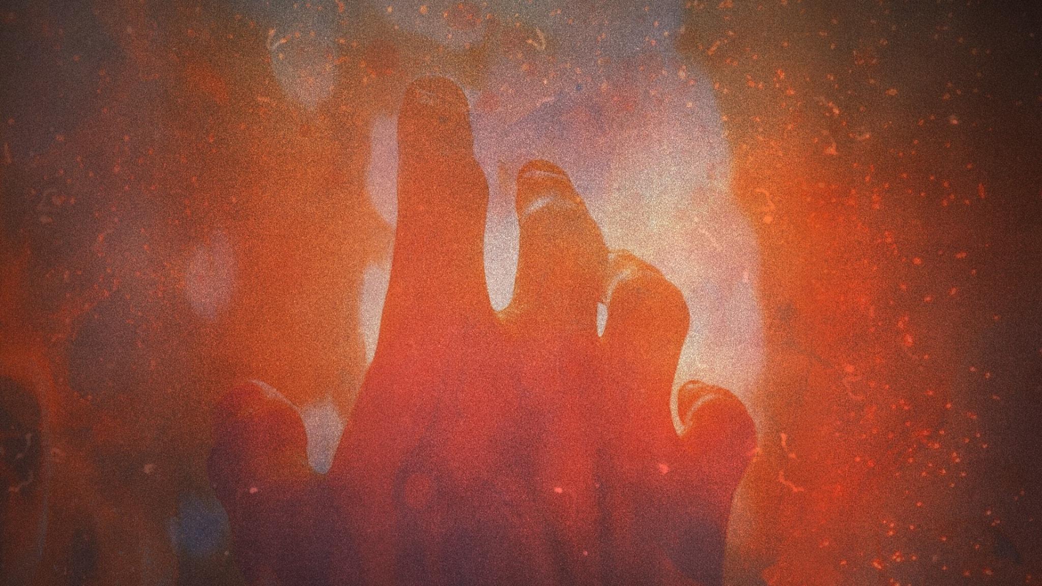 En hand som sträcks upp mot ett hett inferno