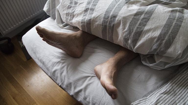 Fötter som sticker ut under ett täcke i en säng.