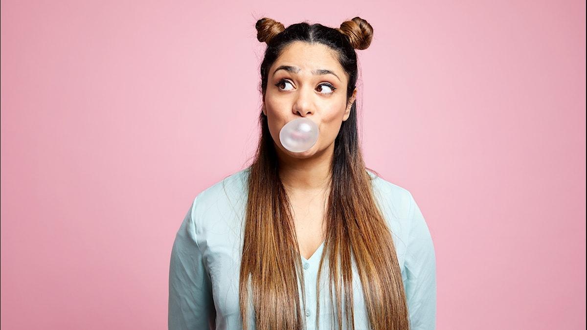Farah står mot en rosa vägg. Hon tuggar bubbelgum och blåser en bubbla.