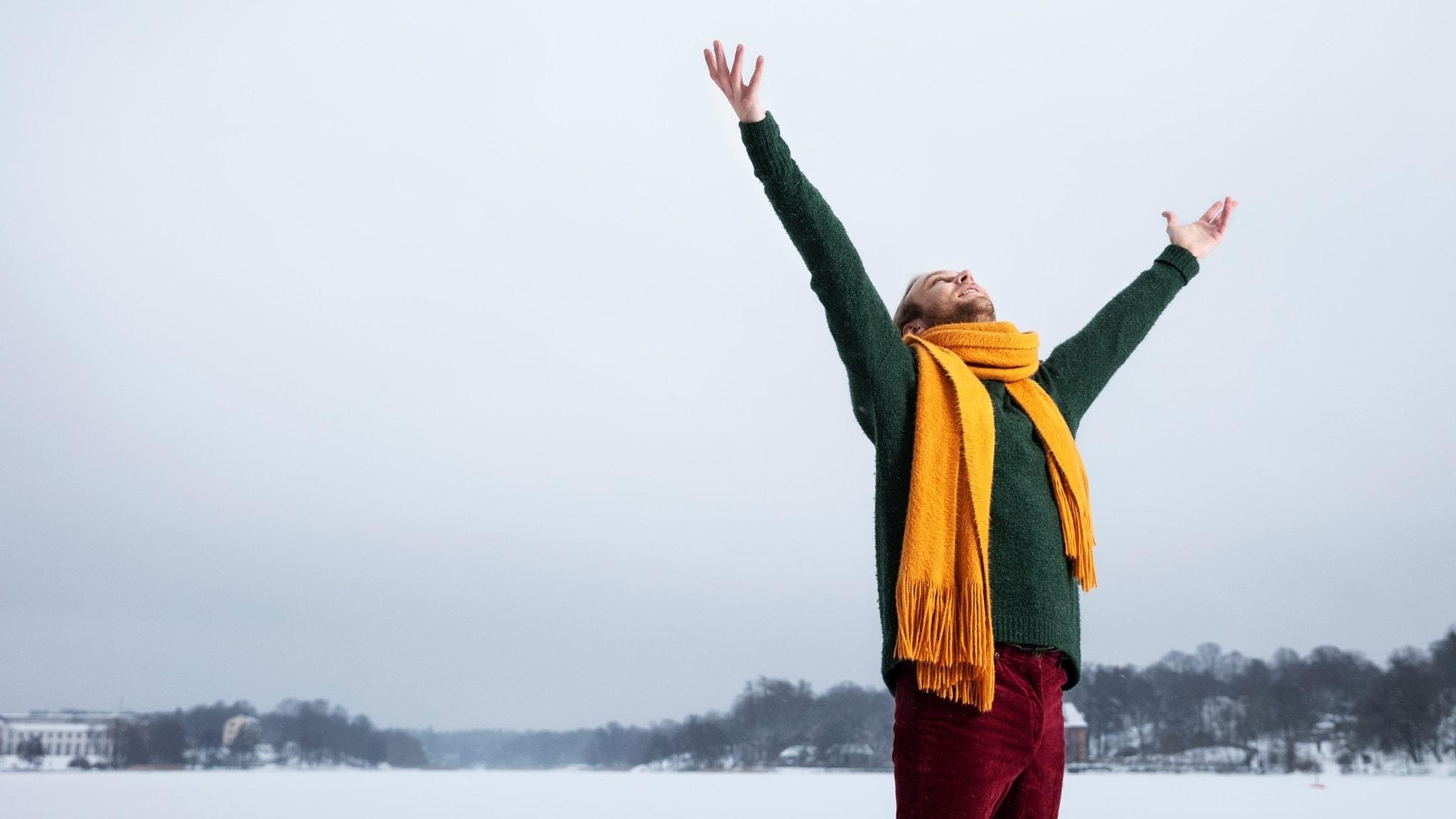 Programledaren Simon Magnusson sträcker upp sina händer mot himlen. En vintergrå januaridag. Han har en stor gul halsduk och en grön ylletröja.