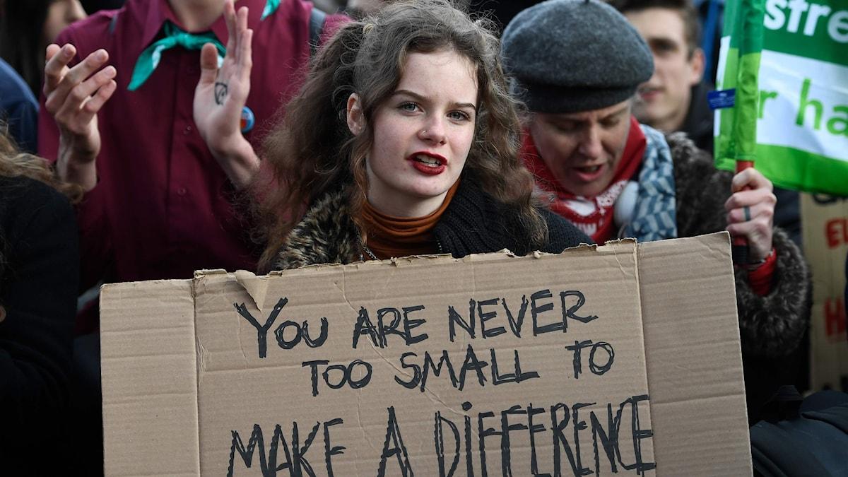 """En tjej håller i en skylt där det står """"you are never to small to make a difference"""""""
