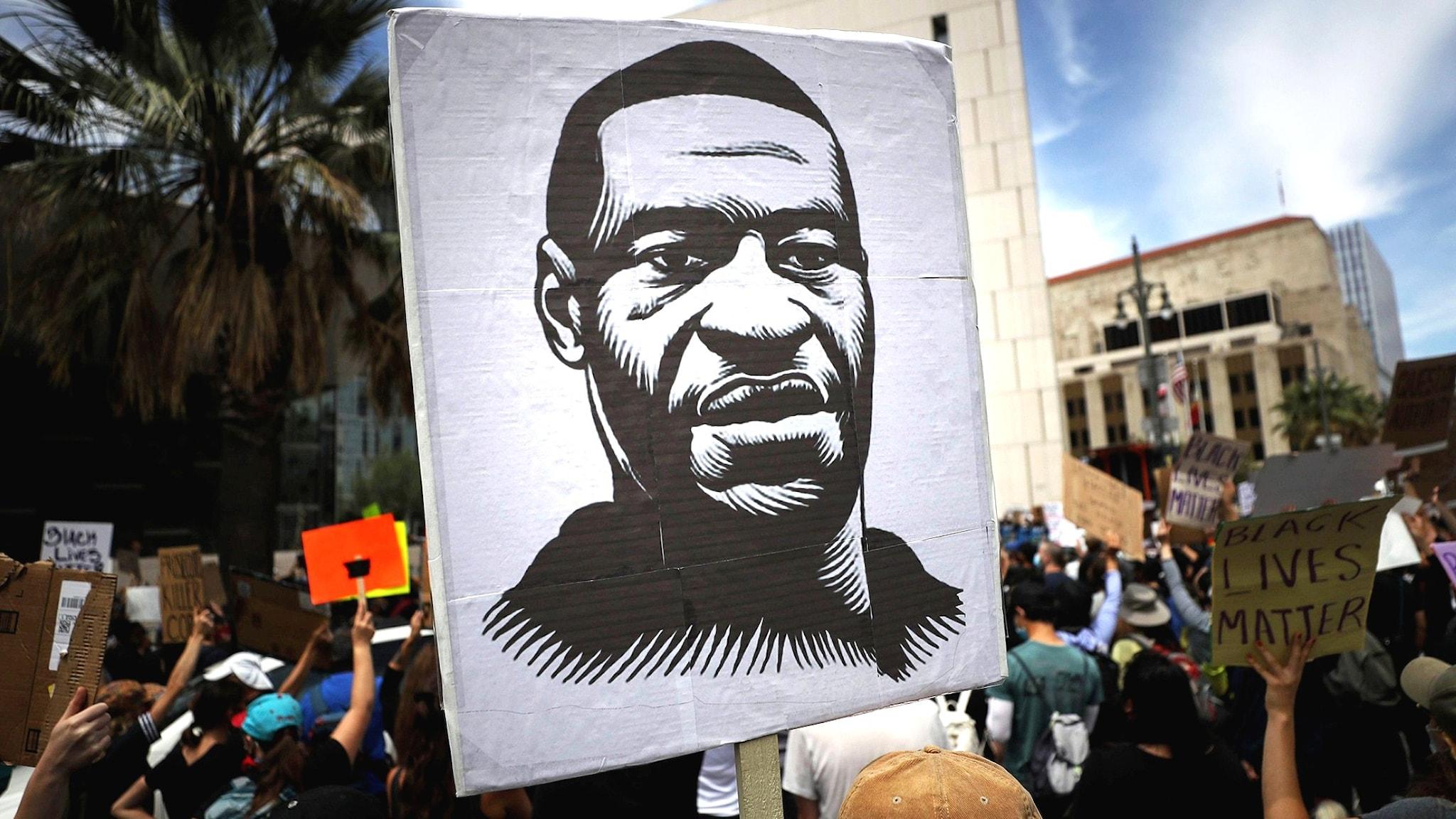 Ett plakat med en målning av George Floyd som dödades av en polis.