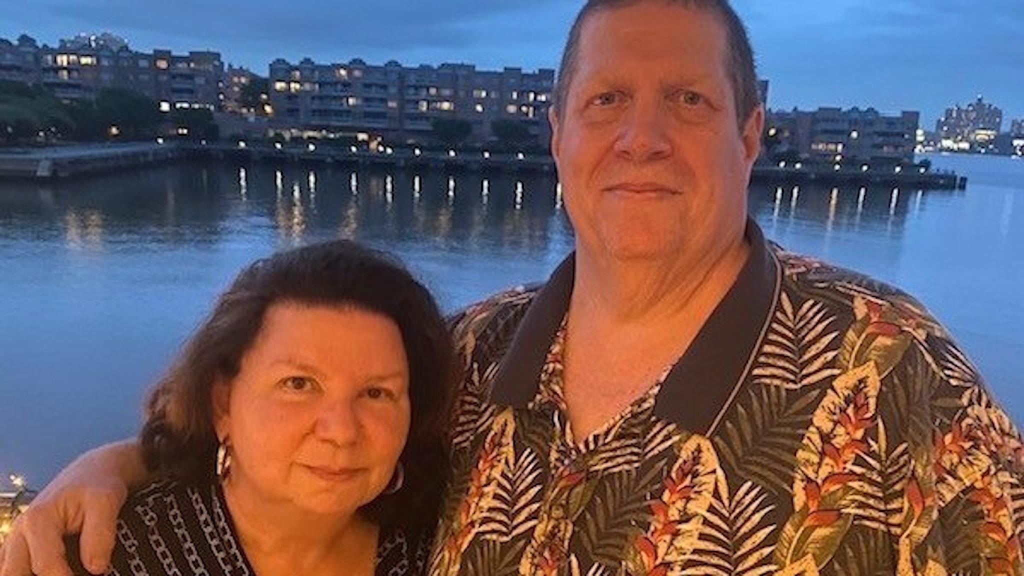 Äkta paret Esther och Jim  på sin bröllopsdag nyligen. Han i en färgglad skjorta och med håret i knut, hon nyfriserad och med en blus. Fotot taget utomhus i New Jersey vid en vik med hus i bakgrunden.