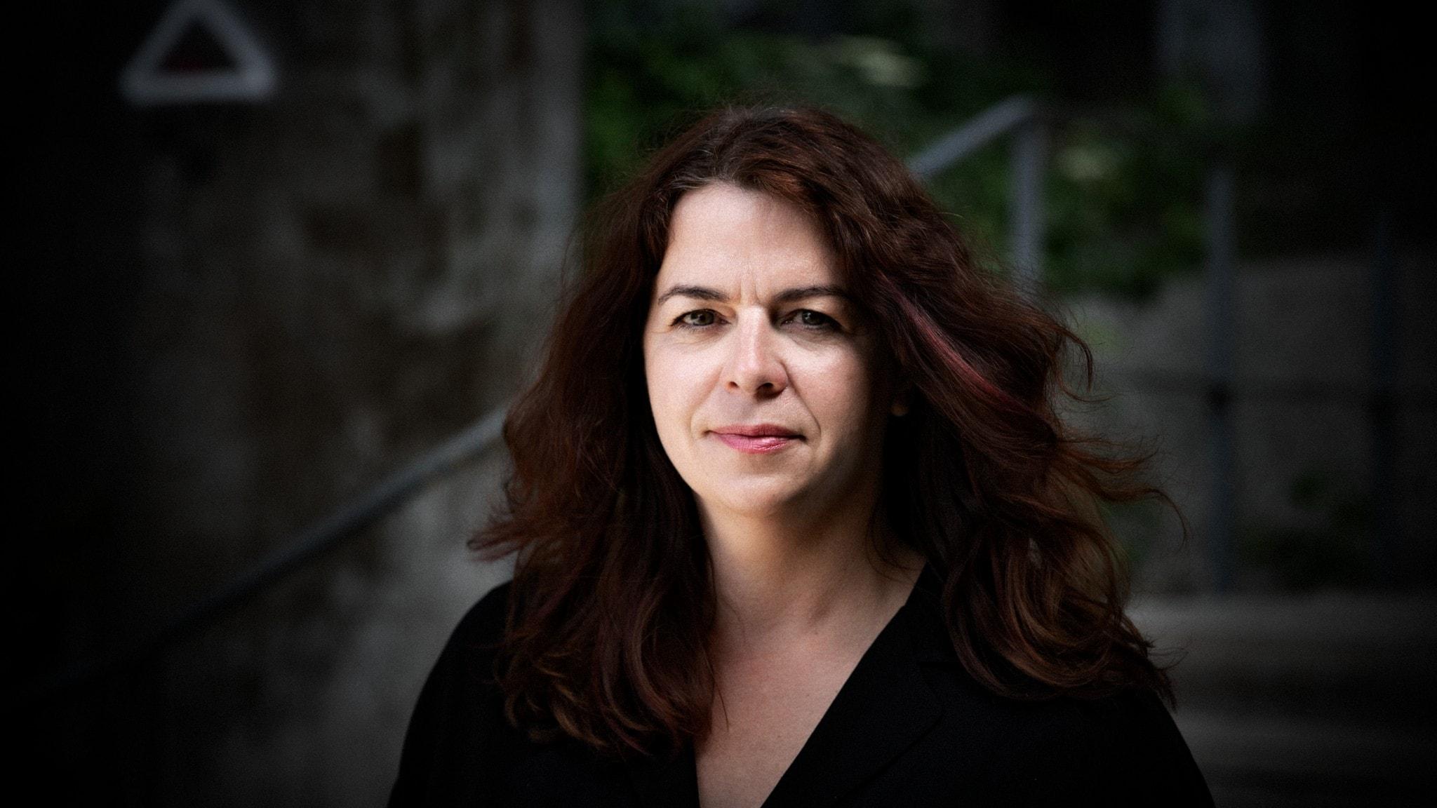 Porträttbild av författaren Åsa Schwarz, med en mörk otydlig bakgrund.