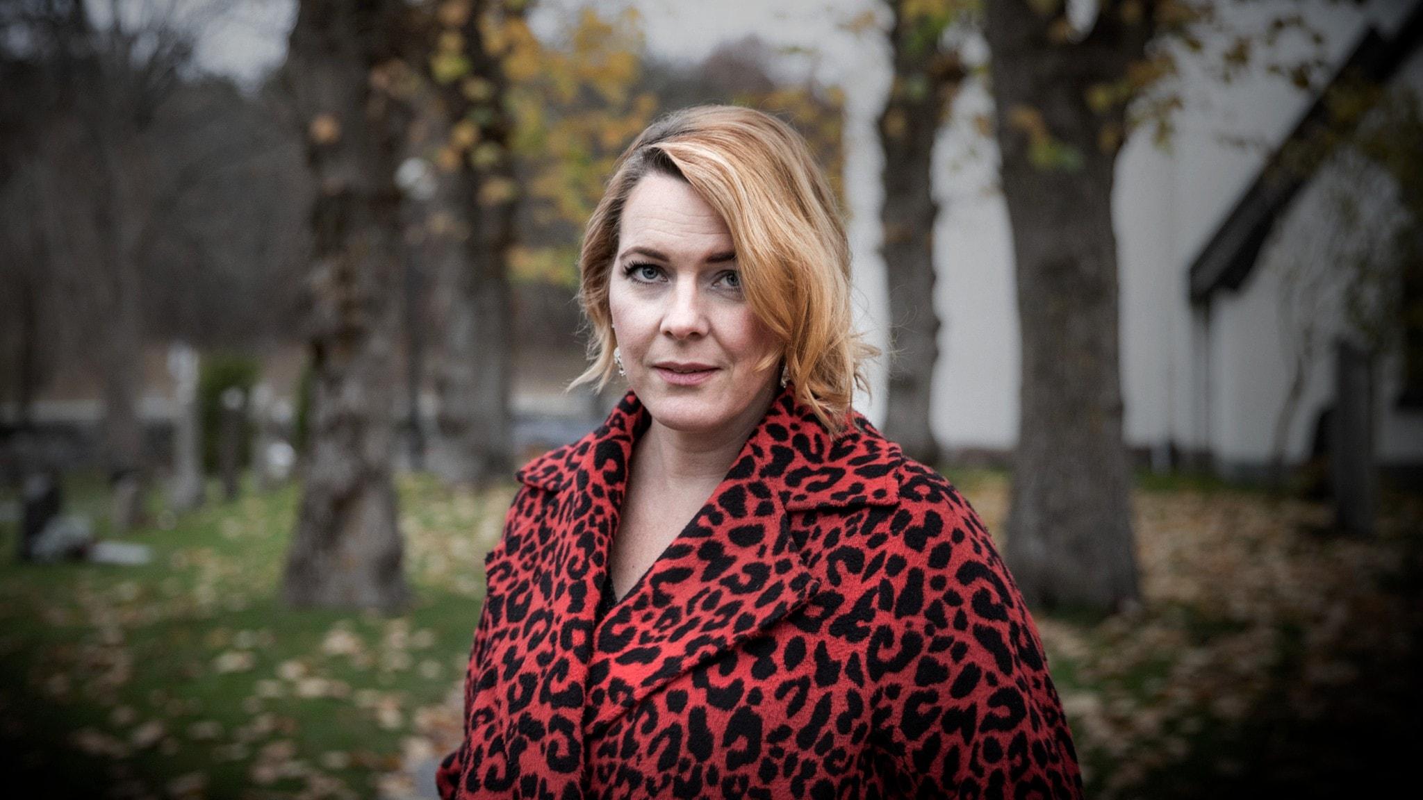 Porträtt av författaren Madeleine Bäck framför en kyrka i höstpräglad utemiljö.