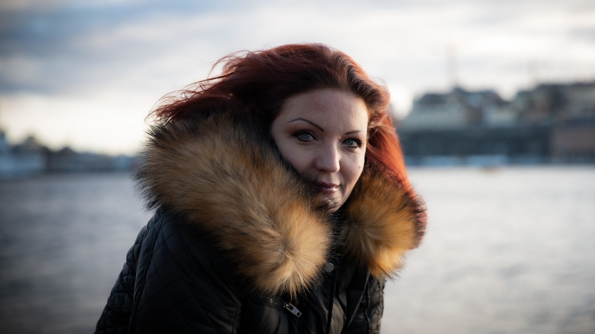 Porträtt av författaren i utomhusmiljö, vid vatten. Suddig Stockholmsbakgrund.