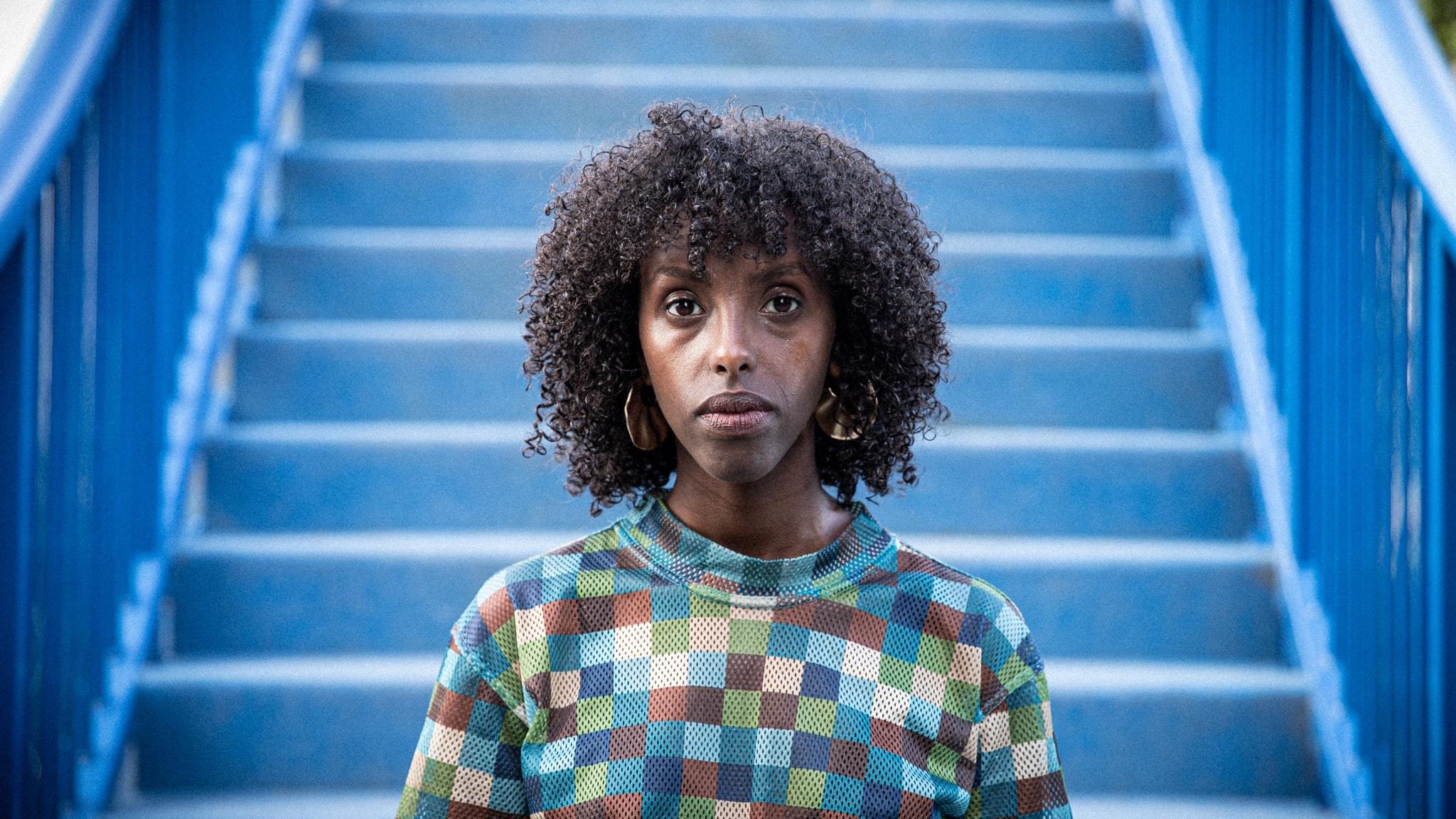 Porträtt av författaren Rahma Omar framför en trappa.