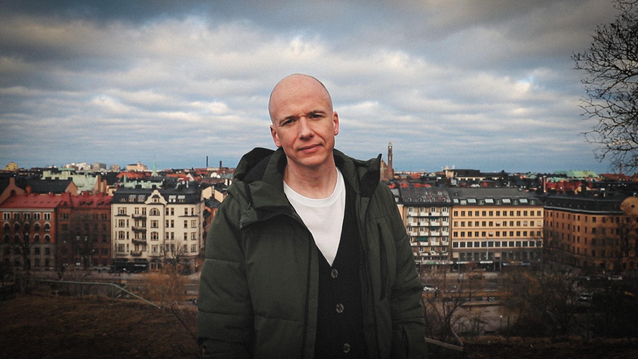 Porträttbild av författaren Daniel Åberg, utomhus med en Stockholmsvy bakom sig.