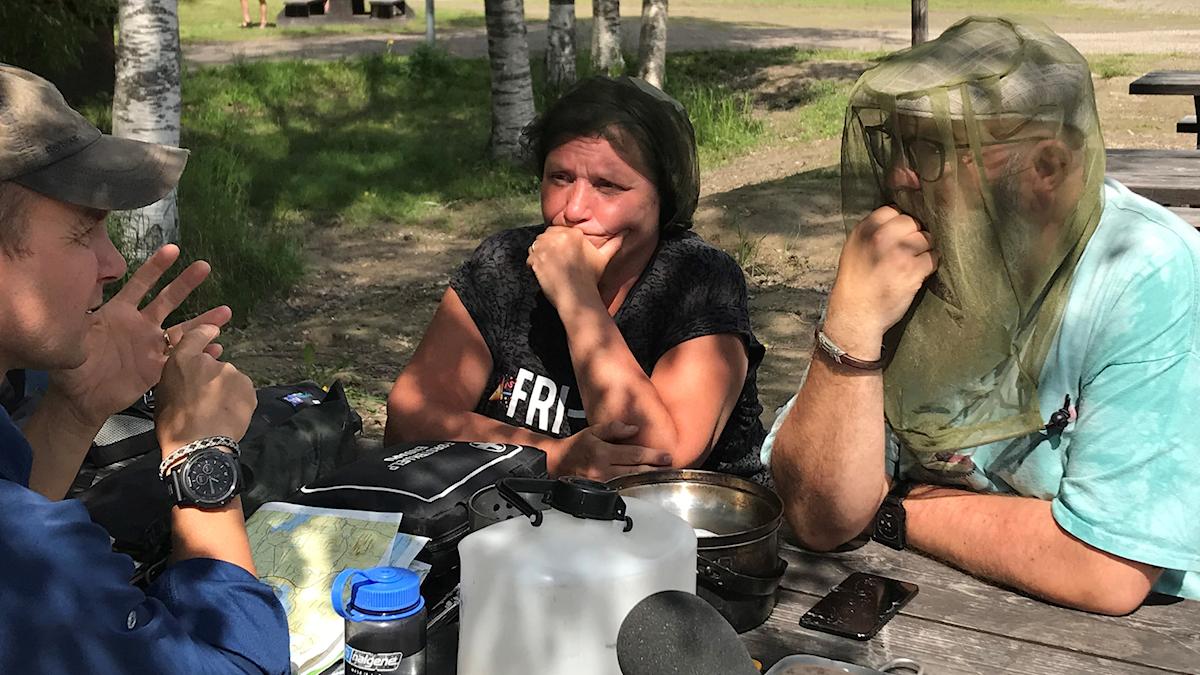 Ulla Öhman och Fredrik Birging med myggnät över kepsen lyssnar koncentrerat på överlevnadsexperten. Foto: Susanne Helsing/Sveriges Radio