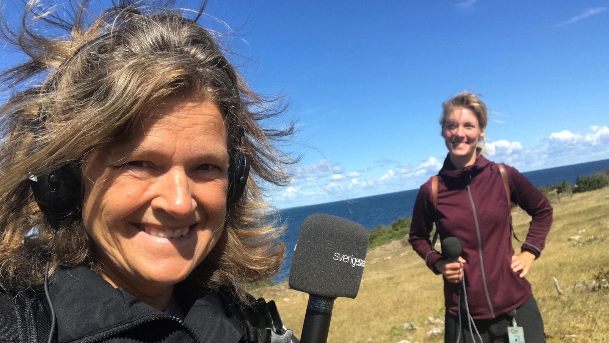 Närbild av reporter Maria med mikrofonen i högsta hugg. I bakgrunden Frida i vinröd fleece. Och så det mörkblå havet.