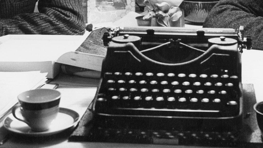 mustavalkokuvassa kirjoituskone ja kahvikuppi